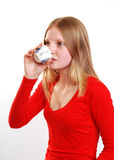Teenager drinking tea. Female teenager drinking tea of coffee from small cup; studio background Royalty Free Stock Image