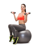 Teenager with dumbbells sitting on fitness ball Stock Photos