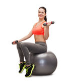 Teenager with dumbbells sitting on fitness ball Royalty Free Stock Image