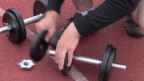 Teenager with dumbbells on sports ground stock video
