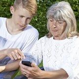 Teenager e senior con lo smartphone Fotografie Stock Libere da Diritti