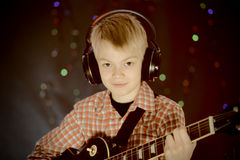 Teenager in earphones and with guitar listens to music Royalty Free Stock Images