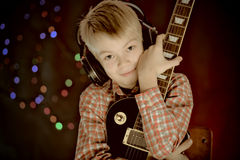 Teenager in earphones and with guitar listens to music Stock Images