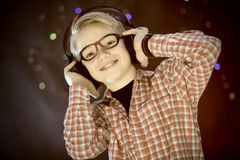 Teenager in earphones and with guitar listens to music Royalty Free Stock Photography