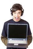 Teenager with earphones holds computer Royalty Free Stock Photography