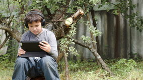 Teenager in earphones using touchpad outdoor. Dolly shot of a teenager boy sitting outdoor in headphones and using tablet computer stock video footage