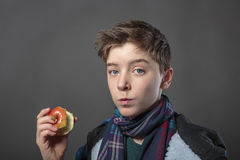 Teenager eating an apple. Portrait of a male teenager eating an apple with winter jacket,  on gray Stock Photos