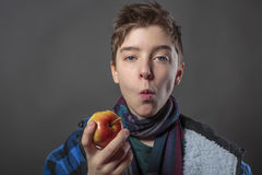 Teenager eating an apple. Portrait of a male teenager eating an apple with winter jacket,  on gray Stock Images