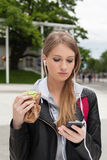 Teenager eating cake looking in phone Stock Photography