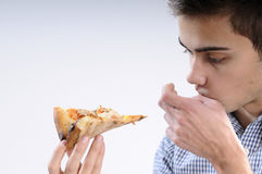 Teenager eating pizza. White, young, handsome man  eating pizza Royalty Free Stock Photo