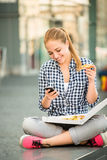 Teenager eating pizza looking in phone Stock Photo