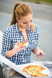 Teenager eating pizza looking in phone Stock Photos