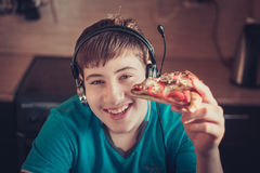Teenager eating pizza sitting at a laptop. Stock Photos