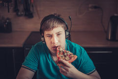 Teenager eating pizza sitting at a laptop. Royalty Free Stock Image
