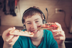 Teenager eating pizza sitting at a laptop. Stock Photography