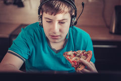 Teenager eating pizza sitting at a laptop. Royalty Free Stock Photography
