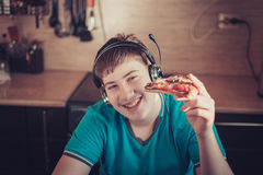 Teenager eating pizza sitting at a laptop. Royalty Free Stock Images