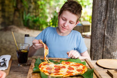 Teenager eating pizza. Teenage boy eating pizza for lunch Stock Photo