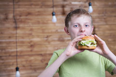 A teenager eating a sandwich Stock Image