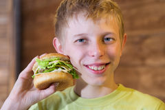 A teenager eating a sandwich Stock Photo