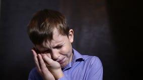 Teenager in einem blauen Hemd, das eine Zahnschmerzen hält stock footage