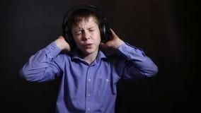 Teenager in einem blauen Hemd in den großen Kopfhörern stock video footage