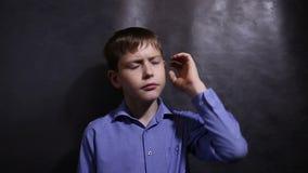 Teenager in einem blauen Hemd denkt das Schauen stock footage