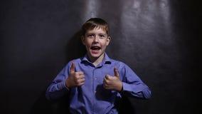 Teenager in einem blauen Hemd zeigt Gestenerfolg stock video footage