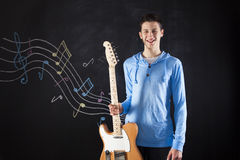 Teenager with an electric guitar. Teenager holding an electric guitar next to a blackboard Stock Images