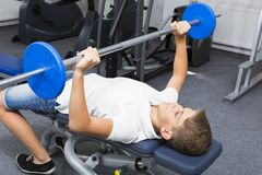 The teenager is engaged in power fitness. In the gym royalty free stock photo