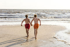 Teenager enjoy running into the ocean Stock Photos
