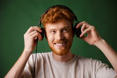 The teenager is enjoying listening to music,. Over green background Stock Photo