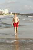 Teenager enjoys jogging along the beach Stock Photos
