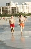 Teenager enjoys jogging along the beach Stock Image
