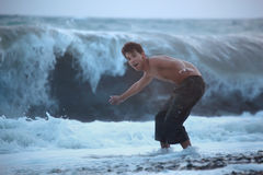 Teenager escaping from sea wave Royalty Free Stock Photography