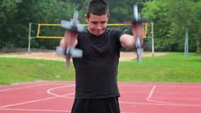 Teenager exercising with dumbbells on sports ground stock video footage
