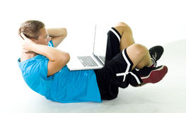 Teenager exercising while using his laptop Stock Image