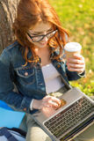 Teenager in eyeglasses with laptop and coffee Royalty Free Stock Photo
