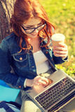 Teenager in eyeglasses with laptop and coffee Stock Photo