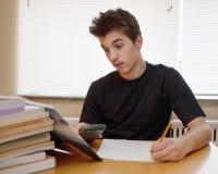 Teenager facendo il suo compito Immagini Stock