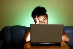 Teenager facendo uso di un computer portatile Fotografia Stock Libera da Diritti