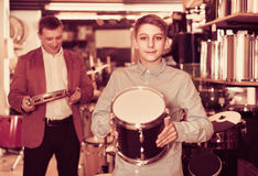 Teenager and father deciding on drum unit in musical shop. Happy teenager and father deciding on drum unit in musical shop Royalty Free Stock Image