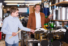 Teenager and father deciding on drum unit in musical shop. Smiling american teenager and father deciding on drum unit in musical shop Royalty Free Stock Photos