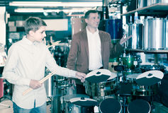 Teenager and father deciding on drum unit in musical shop. Smiling american teenager and father deciding on drum unit in musical shop Stock Photo