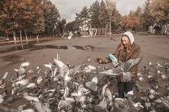 Girl feeding pigeons in the town square .