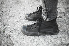 Teenager feet in black gumshoes and jeans Stock Images