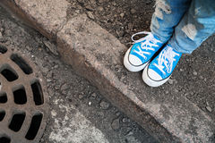 Teenager feet in jeans and blue shoes Stock Photo