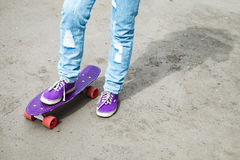 Teenager feet in jeans and gumshoes with skateboard Royalty Free Stock Images
