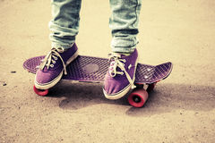 Teenager feet in jeans and gumshoes on skateboard Royalty Free Stock Photo
