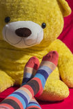 Teenager feet with a teddy bear on background. Colored socks on teenager feet with a teddy bear on background Royalty Free Stock Photos